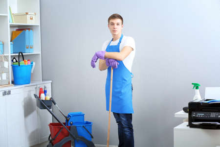Young man with cleaning equipment standing at office Stock Photo