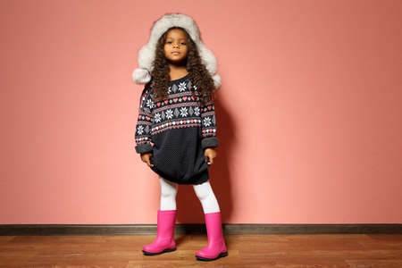 Cute little African American girl in fur hat against pink wall. Fashion concept