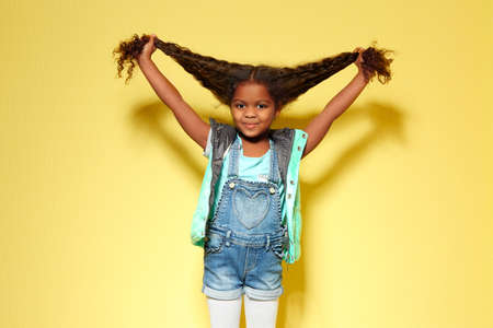 Cute little African American girl in denim against yellow wall. Fashion concept
