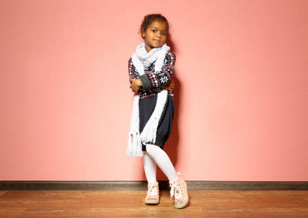 Cute little African American girl in dress against pink wall. Fashion concept Stock Photo