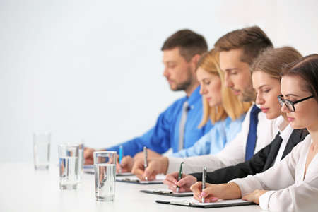 Human resources team sitting in a row at table in office
