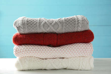 Stack of warm winter clothes on blue wooden background 版權商用圖片