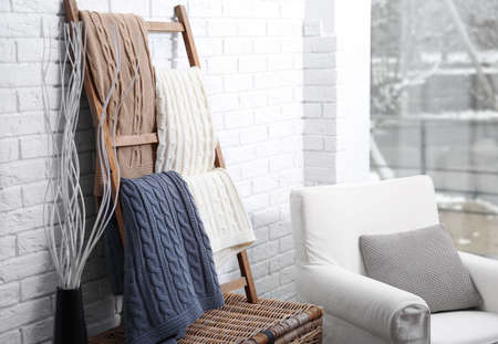 Knitted plaids hanging on decorative ladder
