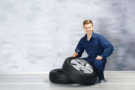 Young mechanic in uniform with wheels, on gray background