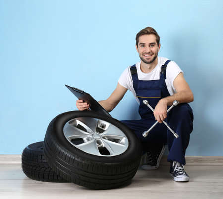 Young mechanic in uniform with spanner and wheels, on blue background