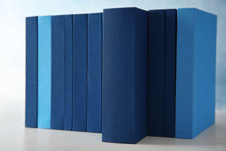 Set of books in row on blue background, closeup