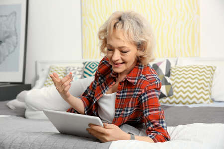 Senior woman making video call from tablet computer at home