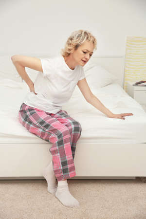 Senior woman suffering from backache while sitting on bed at home