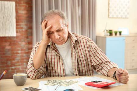 Senior man calculating taxes at home