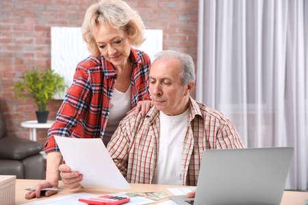 Senior couple calculating taxes at home