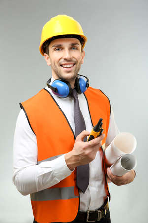 Handsome engineer with portable radio transmitter and drawings on light background