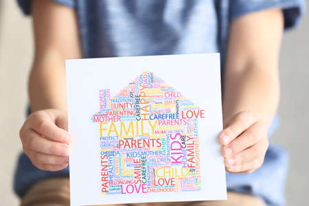 Child holding drawing consisting of words, closeup. Adoption concept