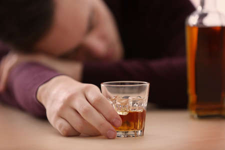 Handsome depressed man drinking whisky at home