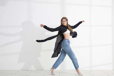 Young extravagant model near light wall 스톡 콘텐츠