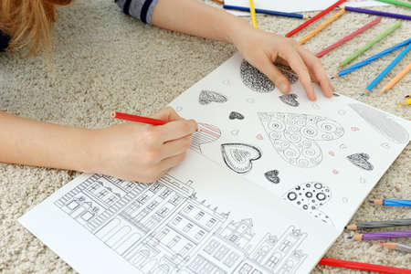 Young woman sitting on floor with coloring pictures for adults