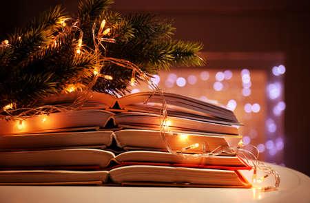 Stapel open boeken, naaldtak en slinger, close-up
