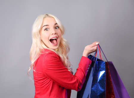 Beautiful young woman with shopping bags on color background Stock Photo