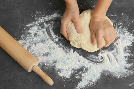 Woman kneading dough on kitchen table, close up