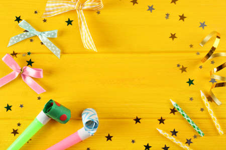 Bright confetti and festive fife on wooden yellow background Stock Photo