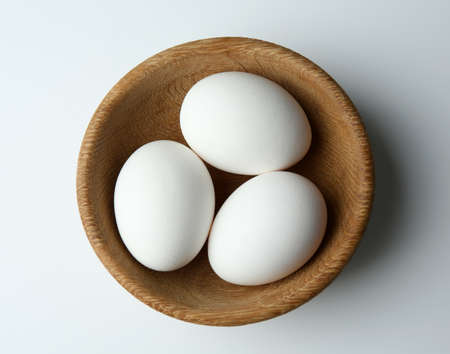 Raw eggs in bowl on white background