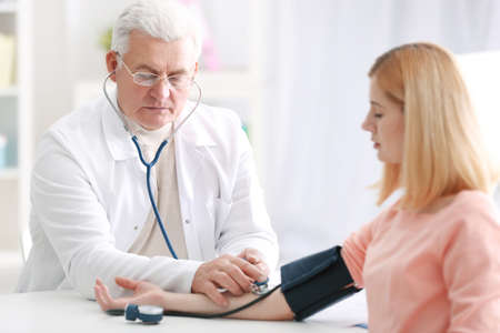 Doctor measuring blood pressure of patient Stock Photo