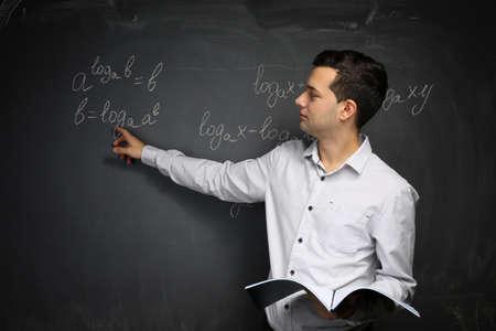 Handsome young teacher explaining math formulas written on blackboard