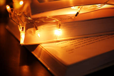 Closeup view of open books and beautiful garland on table Stock Photo