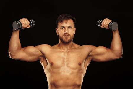 Sporty young man with dumbbells on black background
