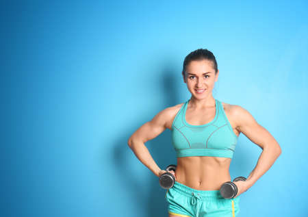 Sporty young woman with dumbbells on color background
