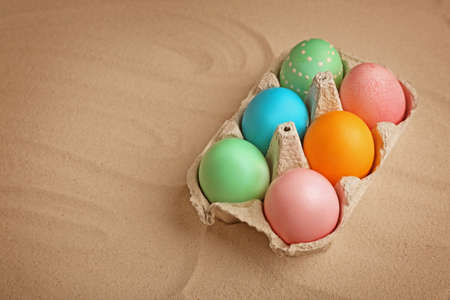 Colorful Easter eggs in carton box on sand