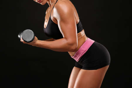 Sporty young woman with dumbbell on black background, closeup
