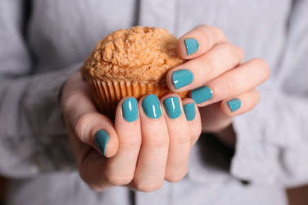 Female hands with beautiful nail art holding muffin, closeup Stock Photo