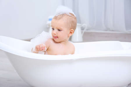 Little baby boy washing in bathtub indoors