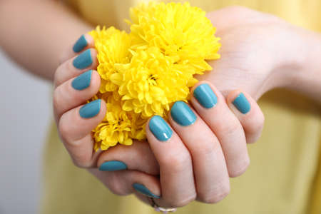 Female hands with beautiful nail art holding flower, closeup