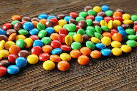 Tasty colorful candies on wooden table, closeup