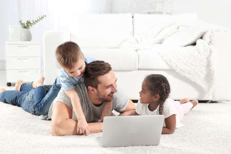 Happy father with interracial children lying with laptop on floor