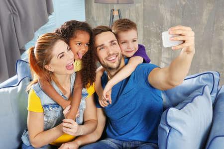 Happy interracial family making selfie on sofa