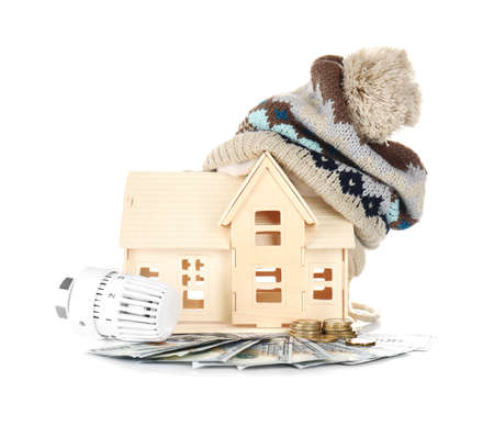 Savings concept. House model with hat, money and heating thermostat on white background Stock Photo