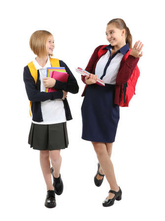 Two cute girls in school uniform on white background