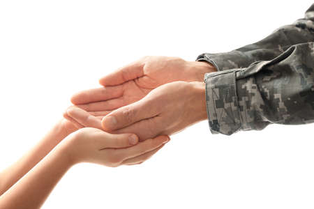 Hands of soldier and child on white background