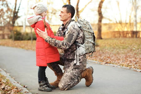 Soldier in camouflage with his daughter outdoors