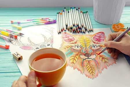 Woman sitting at table with coloring pictures for adults, closeup Stock Photo