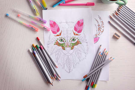 Composition of colouring picture, pencils and pens on wooden table