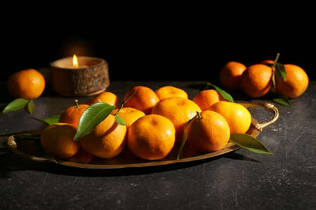 Vintage tray with tangerines on dark background