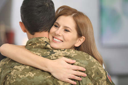 Soldier in camouflage hugging his wife at home