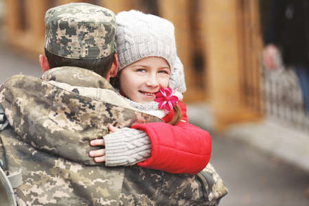 Soldier in camouflage hugging his daughter outdoors