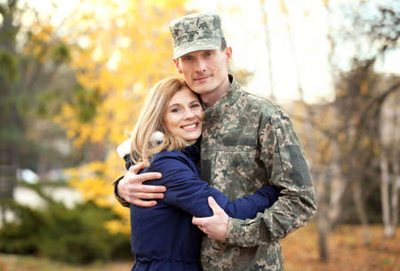 Soldier in camouflage hugging his wife outdoors Stock Photo