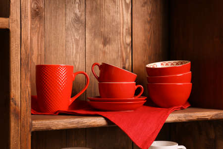 Wooden shelves with red rustic dinnerware