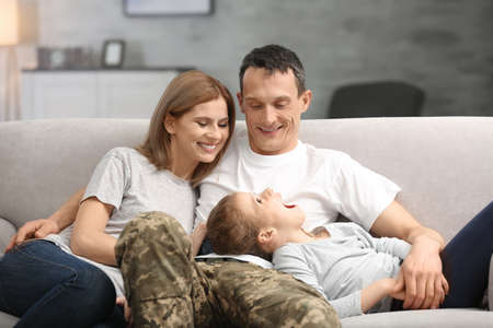 Military father with his family on sofa at home