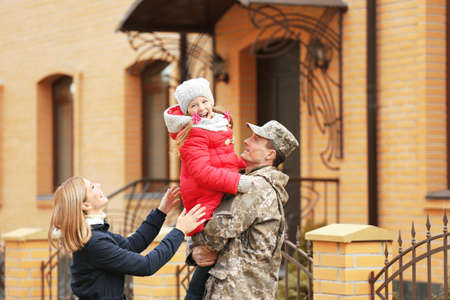 Happy soldier with his family outdoors